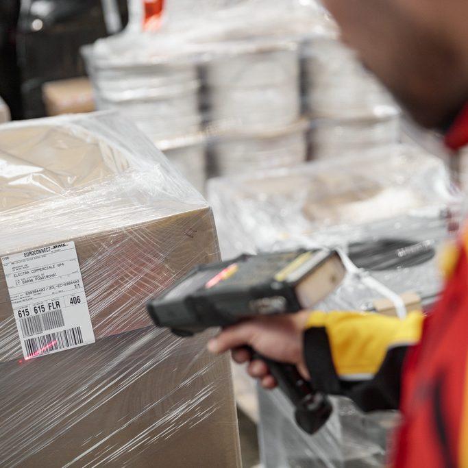 funcionário DHL a ler etiqueta com o laser
