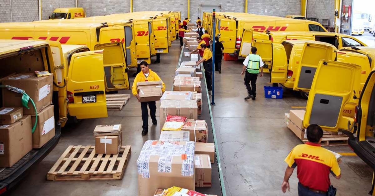 Operação DHL com vários estafetas a carregar as encomendas nas carrinhas