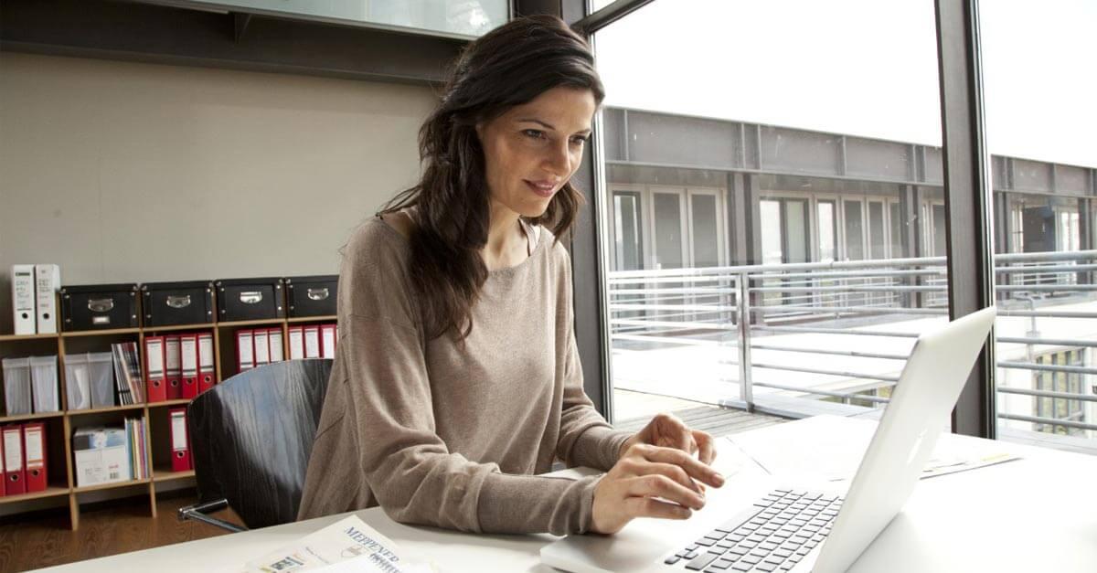 Senhora sentada a uma secretária a trabalhar no computador